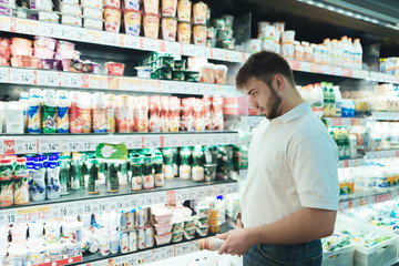 A man chooses yogurt in a supermarket. The buyer selects dairy products. in the shop. A man buys food in a supermarket.