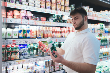 An emotional man chooses yogurt in the milk department of the supermarket. The man buyer buys the products in the store. Selection of products in the supermarket.