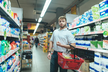 A man with a product basket strolls around the supermarket and chooses goods. A man buys food in a supermarket.