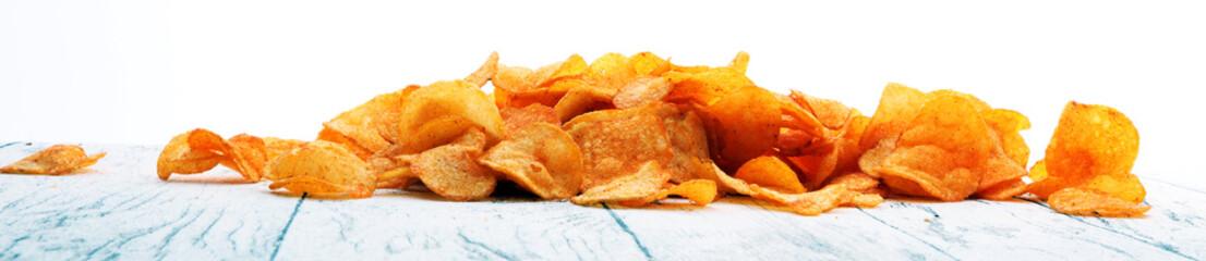 Crispy potato chips. Paprika chips on white wooden background.