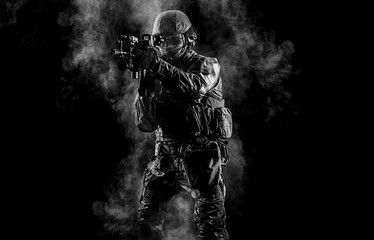 American soldier in combat ammunition with weapon in the hands of equipped laser sights is in battle order