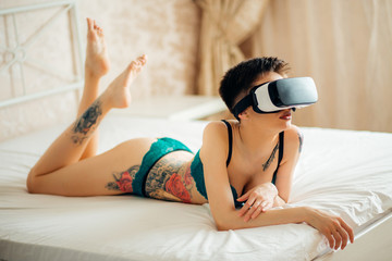 Beautiful woman wearing Lingerie using vr-goggles in bed.