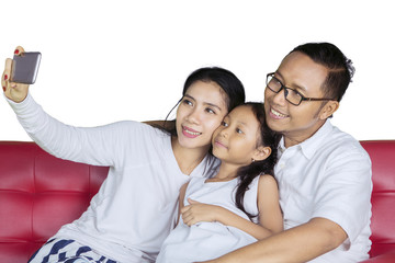 Young family taking a picture together on studio