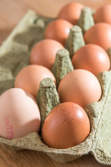 Close-up view of raw chicken eggs in egg box on  oak wooden background