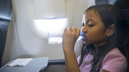 Little girl drinking water in airplane