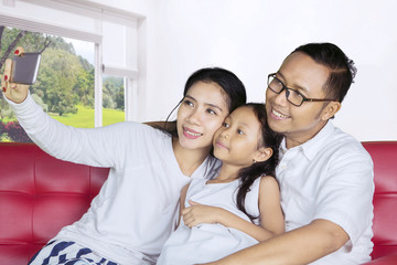 Happy parents with child taking photo at home