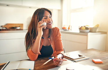 Smiling female entrepreneur talking on a cellphone in her kitche
