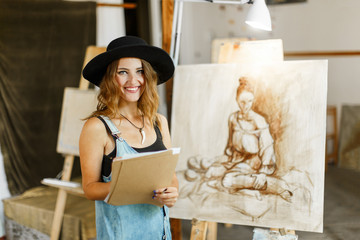 Beautiful long hair artist girl, in a black hat and denim dangarees, considering the idea of her picture before the easel