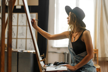 Female artist wears black hat draw picture indoor the studio Wall mural