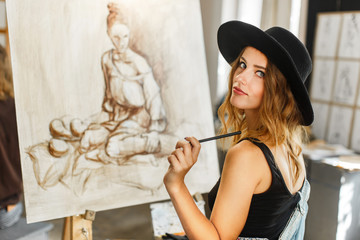 Female artist wears black hat draw picture indoor the studio