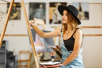 Female artist wears black hat draw picture indoor the studio