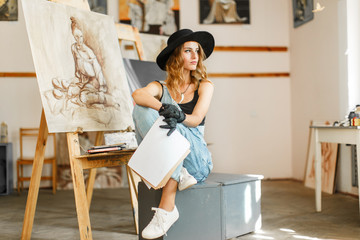 Female artist wears black hat posing near picture indoor the studio