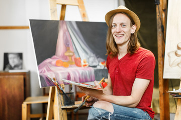 Long hair caucasian male artist, in a light brown hat, smiling during painting in the studio