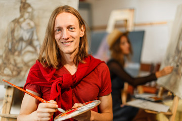 Long hair caucasian male artist smiles near the picture in the studio