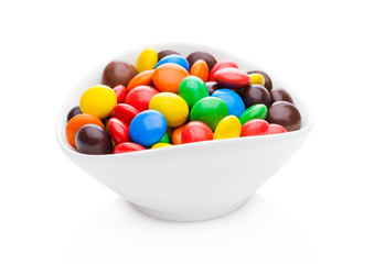 Round colorful coated sweet candies in white bowl