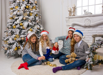 Children in Santa caps are decorate a Christmas tree in a room.