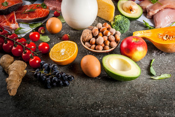 Healthy diet background. Organic food ingredients, superfoods: beef and pork meat, chicken filet, salmon fish, beans, nuts, milk, eggs, fruits, vegetables. Black stone table, copy space