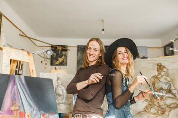 Young artists couple smiles near the picture in the studio