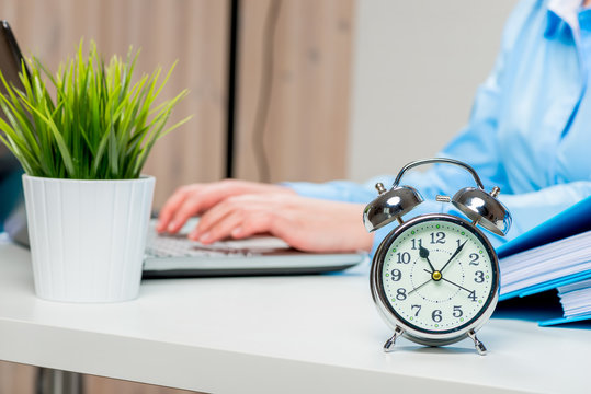 An alarm clock on the desk in the office and an accountant out of focus