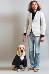 Studio shot of a young man and dog in busness suit