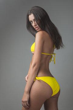 white Caucasian brunette girl female model attractive fit skinny sexy beautiful posing on studio grey background yellow bikini
