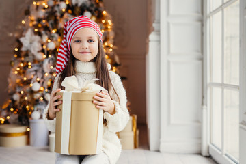 Indoor shot of pleasant looking small kid with blue charming eyes, wears santa hat, holds present in wrapped box, sits over decorated New Year background. Childhood, celebration concept