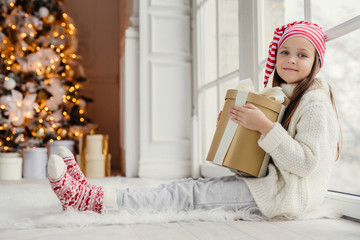 Portrait of adorable pleasant looking girl wears comfortable warm clothes, holds wrapped gift box, recieves congratulations with New Year from parents and relatives, has pleased expression