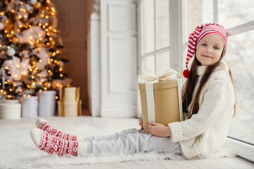 Cute lovely girl with present, sits near window in living room, looks delightfully into camera, admires wonderful beautiful decorated fir tree, has good mood and holidays. New Year concept
