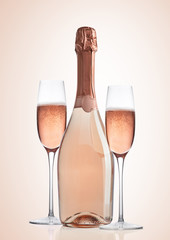 Bottle and glasses of pink rose champagne on pink