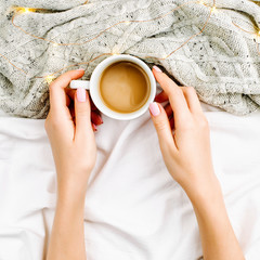 Female hands hold Cup of coffee on bed with warm plaid. Copy space. Flat lay, top view