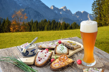 Brotzeit mit einem Hefeweißbier rustikal in den bayerischen Alpen serviert -  Hearty snack with a yeast wheat beer served in the Bavarian Alps