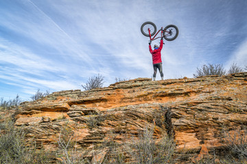 male rider lifting his fat bike on a sandstone cliff in Colorado foothills, fall scenery