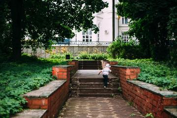 a little boy runs up the stairs