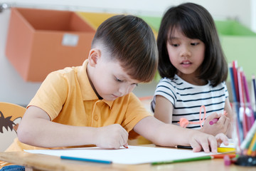 Boy and girl drawing color pencils in kindergarten classroom, preschool and kid education concept