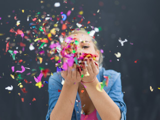 Foto op Textielframe Carnaval woman blowing confetti in the air isolated over gray