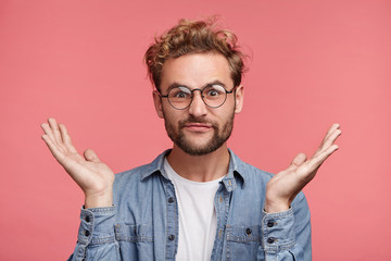 Bearded Caucasian male has hesitatnt and displeased expression, gestures doubtfully, has no answer on difficult question, being puzzled or confused. Uncertain fashionable guy over pink background