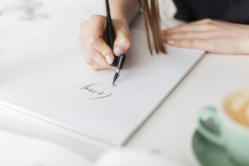 Close up photo of woman hands holding pen and writing  beautiful notes on paper isolated
