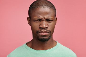 Headshot of sullen moody glum African American man frowns face, being very obused or displeased after conversation with boss. Unhappy upset discontent dark skinned man isolated on pink background