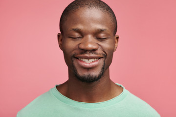 Headshot of glad cheerful dark skinned man closes eyes, smiles happily, going to recieve present, celebrates his work promotion or anniversary, pleased to hear positive words and congratulations