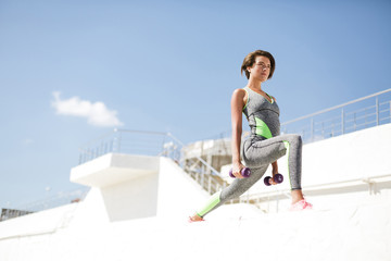 Portrait of thoughtful woman with brown short hair in modern gray sport suit and pink sneakers standing and doing exercise with dumbbells while dreamily looking aside