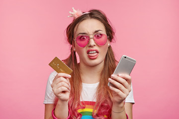 Beautiful young female model with pony tails makes grimace as holds modern mobile phone and credit card, does shopping online, pays for goods, displeased with high prices. Online payment concept