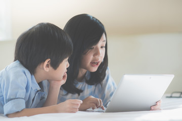 Asian children lying in bed and using laptop
