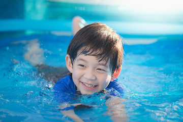 Boy swimming and playing in a pool