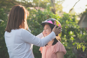 mother wears a bicycle helmet to her daughter