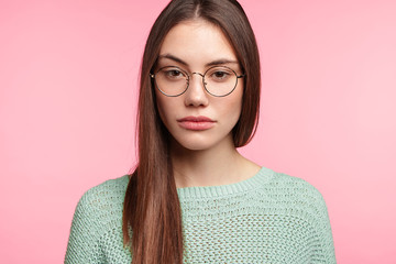 Portrait of attractive young female with Asian appearance wears spectacles, loos seriously at camera, has sad expression, wants sleep, listens to lecture attentively, isolated over pink background