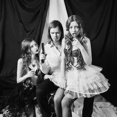 A man with long hair in a white shirt sits on a chair. Gangster with a gun on a black and white background. Two young red-haired girl with long hair with lollipops in hands in underwear and stockings.