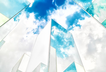 Bottom view of reflection of blue sky on building mirror. Abstract background.