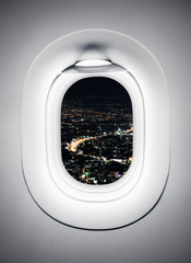 Night city at airplane window