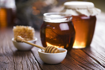 Foto op Canvas Thee Honey in jar with honey dipper on wooden background