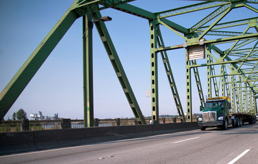 Green big rig semi truck with flat bed trailer for transporting over sized loads going through the bridge